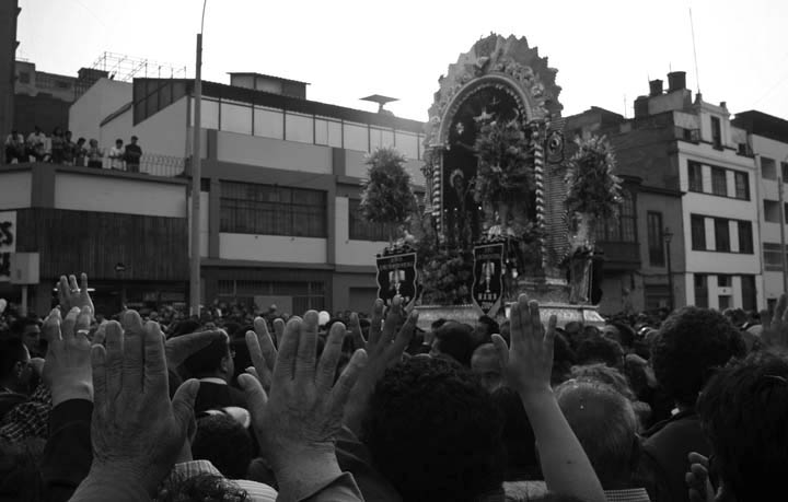 The faithful greet the procession bearing the image of Our Lord of Miracles.