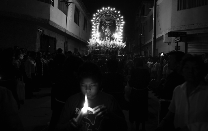 A boy lights a candle as he joins a procession for Senor de los Milagros (Our Lord of Miracles).