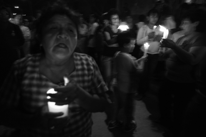 A woman sings as the procession passes through her neighborhood.