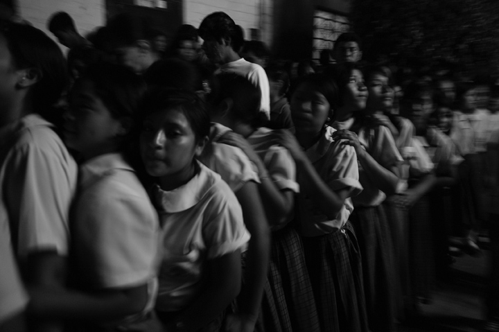 School girls walk in a tightly knit line as they follow the procession.