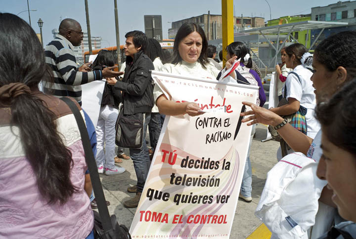 A Peruvian woman is wearing a sign that denounces racism as she distributes literature to pedestrians on a crowded street.