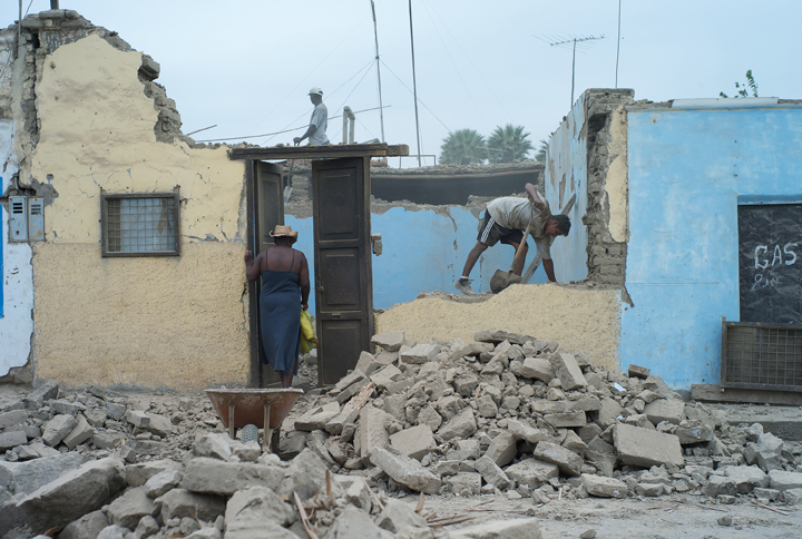 An Afro-Peruvian woman walks into a house where the roof is gone and the walls are heavily damaged; a worker tears down the remains of a wall.