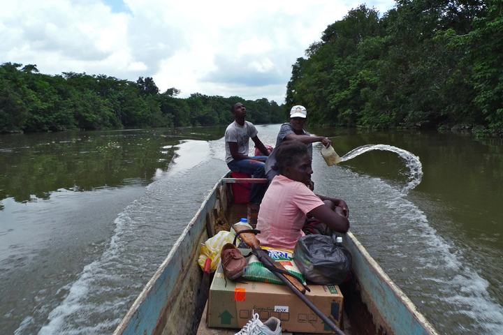 An Afro-Ecuadorian man operates a small motor-powered boat while another removes water that has leaked into the boat, as a female passenger sits quietly.