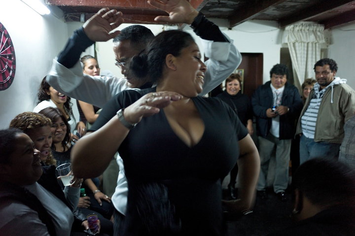 Two Afro-Peruvians (female/male) dance inside a room filled with cheering neighbors.
