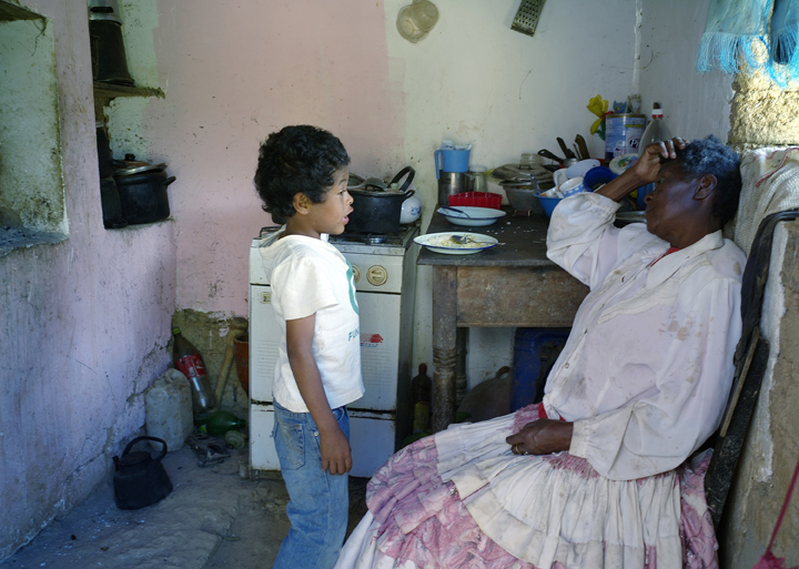 An elderly Afro-Bolivian woman is sitting in a chair in the kitchen while talking to her 7-year old grandson who is standing.