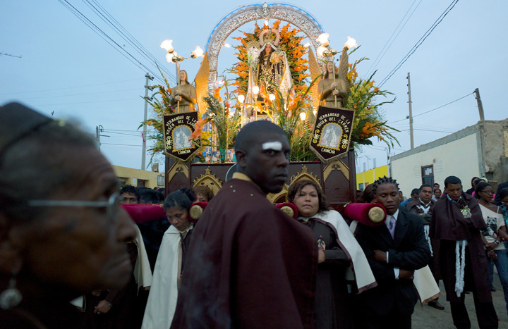 Peruvians carry a religious statue through the streets as both a black woman (observes in the foreground) and a black man (amongst those carrying the statue) are prominent in the photograph.