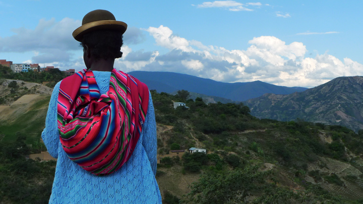 A black woman dressed in colorful attire and a bowler hat, with her back to the camera, looks down on a hill.