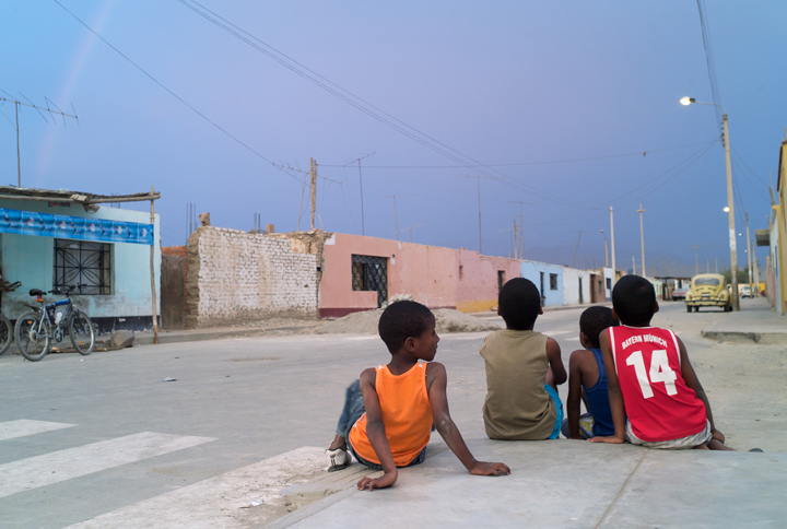 Four young Afro-Peruvian boys are sitting on a curb, on an empty street, observing a rainbow.