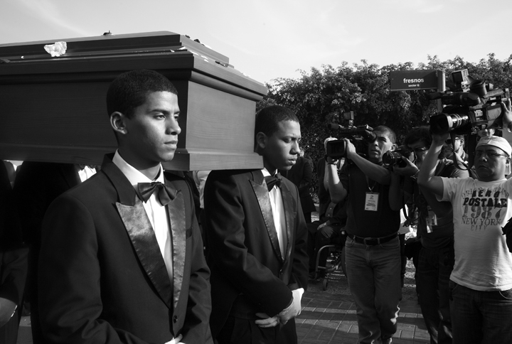 Under the glare of television cameras Afro-Peruvian men (working as camalenque - a vocational identity) carry the casket of slain Peruvian Stephany Flores. Joran van der Sloot, of Holland, confessed to her killing. Afro-Peruvian men are highly sought to carry coffins at the most upscale funerals in Peru. Clad in tuxedos and white gloves they are hired under the belief that their skin-color lends an aura of elegance to the job.