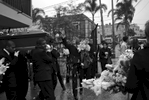 A family member tosses flower petals onto the casket as it is carried to a hearse.