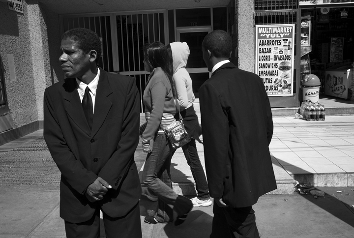 While waiting for a cab to take them to a funeral service Edwardo Alexander Rivas, right, tries to pick up young women as Victor Castillo stands nearby. During the wait Rivas, 24, spent the entire time trying to speak with young and mature women. {quote}I just love women, young or old it doesn't matter,{quote} explained Rivas.