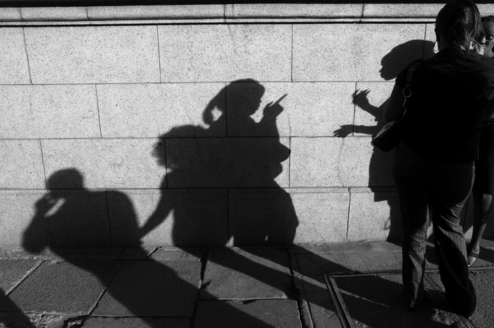 Two women are seen talking on a city street with their shadows, and that of man on his cell phone, visible on a wall.