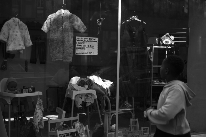 A window front displays and advertises the sale of used baby items.