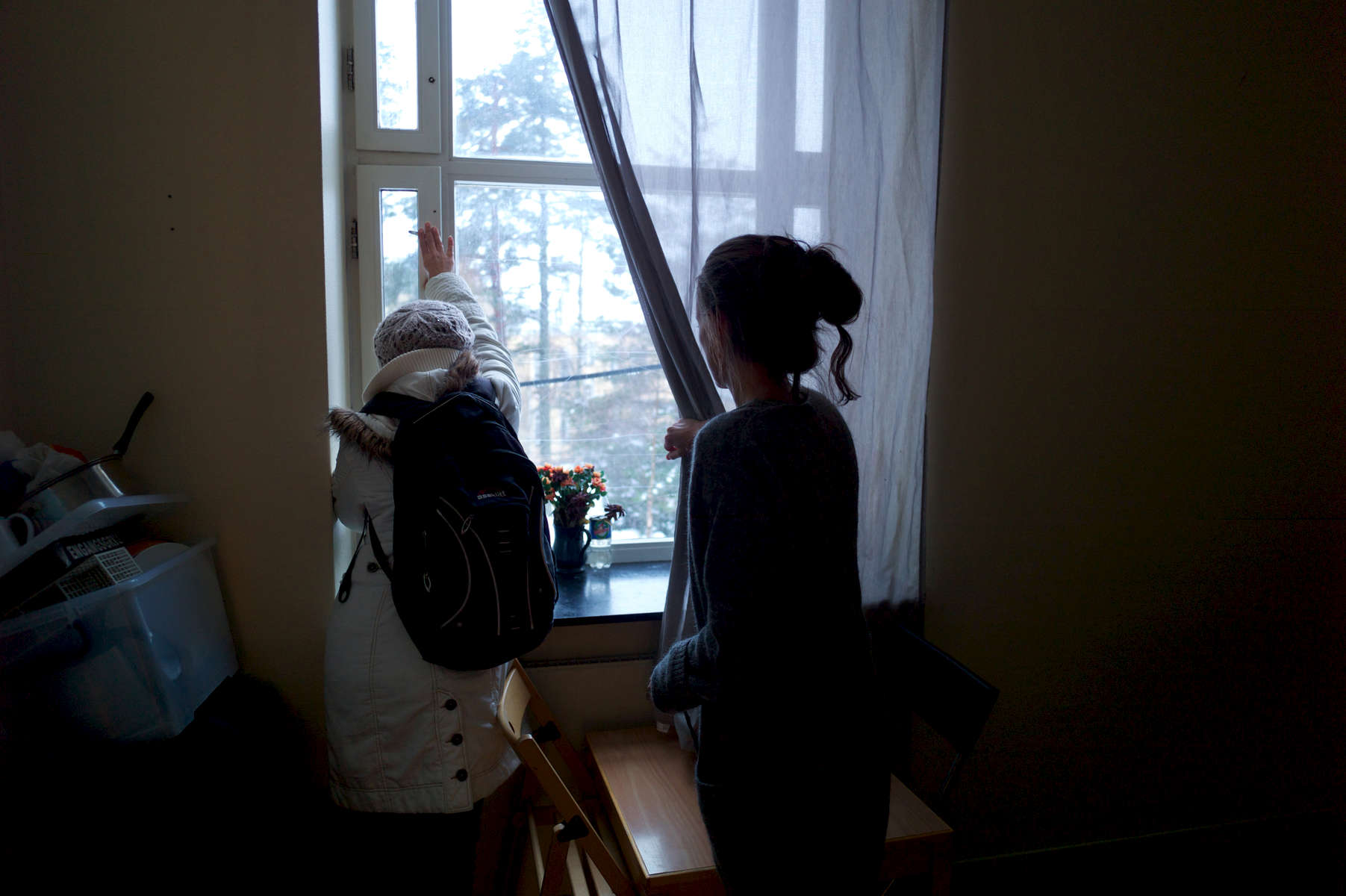 A rejected asylum seeker looks out the window of her darkened room with a refugee camp worker standing nearby.