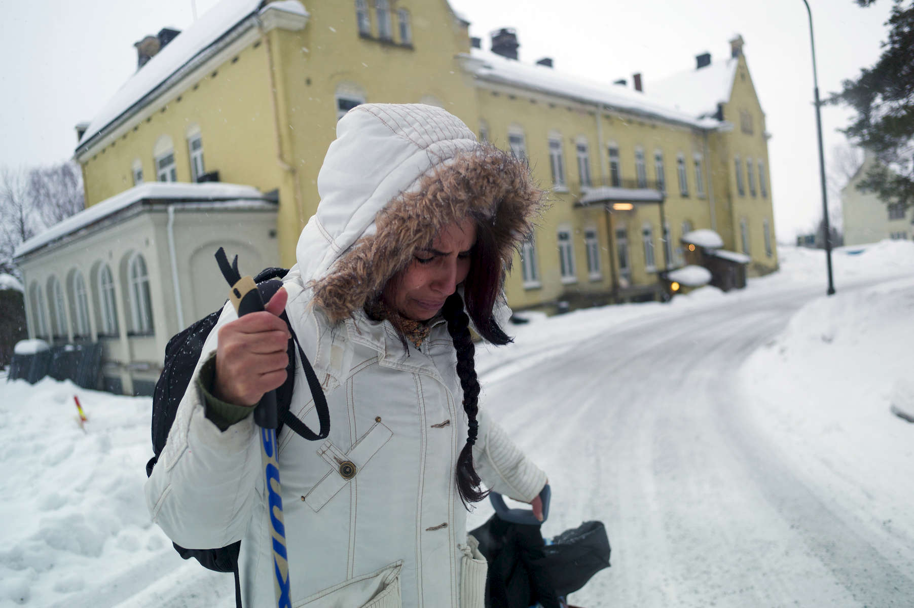 A rejected asylum seeker crys while pulling her luggage through the snow.