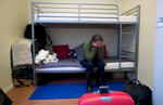 A rejected asylum seeker sits crying on the bottom of a bunk bed.