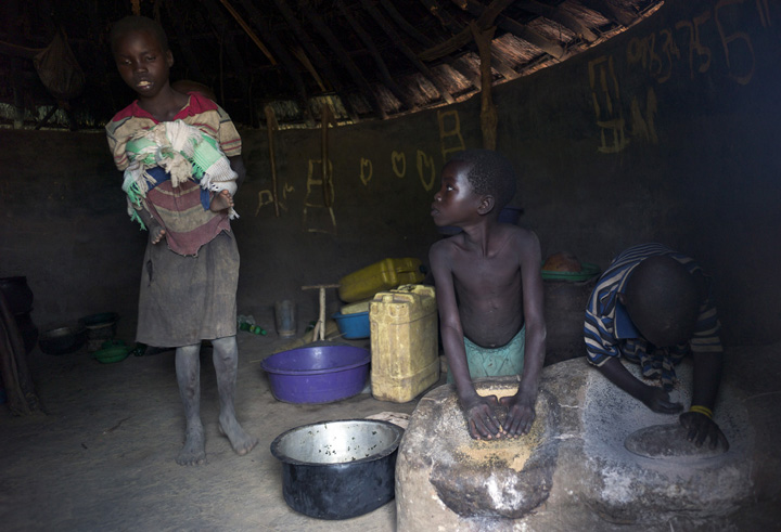 Agnes Alimo, 10, left, returned home from school with her one-year old brother (Regan Kidaga) because he would not stop crying. Her sister Vicky Auma, 7, center, and a neighborhood boy, Ogen, 6 (who didn't know his last name) stayed home from school to crush groundnuts. The hidden cost of schooling is overwhelming in the post-conflict Acholi sub-region (northern Uganda). Children constitute an invaluable source of stopgap labour for households re-establishing livelihood strategies in the aftermath of twenty years of war.