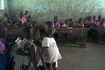 Primary one grade students lineup to have their school work examined by their teacher at Acutomer Primary School.