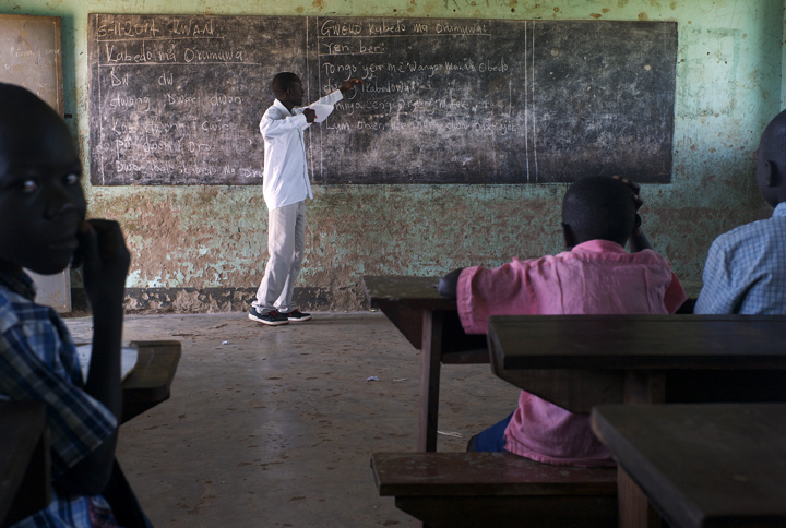Charles Okot, 23, teaches literacy in Kwan (the local language) to primary one grade students at Acutomer Primary School. The students range in age between six and eight.
