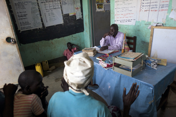 Alex Opira, right, headmaster at Acutomer Primary School, tries to resolve a problem about overpaid school fees involving Pauline Akwero, foreground, her son, Robert Mugisha, 11, seated on the floor - far left, and a teacher who's not present.