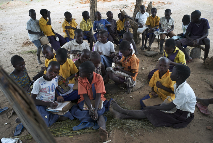 Students study outdoors under a tree at Obira Primary School.