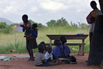 While taking notes a 10-year old girl paces with her one-year old brother on her back, at an outdoor classroom. A teacher stands near a wood board with five students seated on the ground.