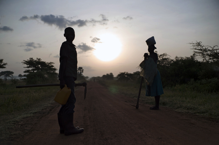 During sunrise Phillips Oluoch, 12, left, who had to stop attending school because his family could not afford school fees, waits with his mother for several village women, as they make their way to work in the field.