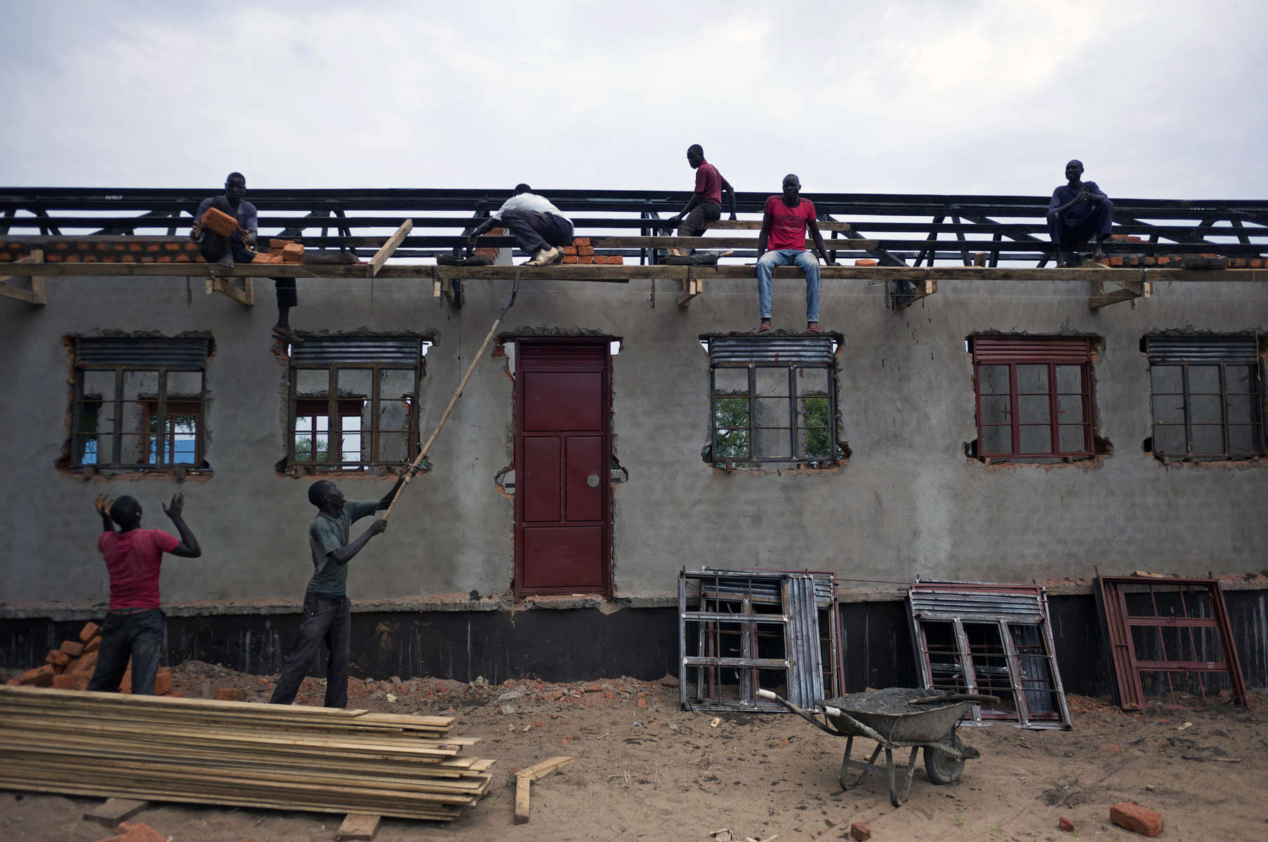 Several men are sitting atop an unfinished school building as others on the ground hand them cement blocks.