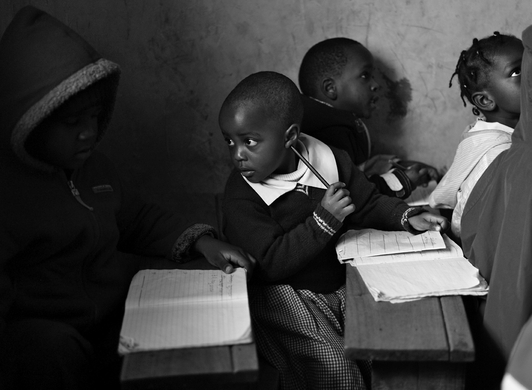 Ebsen Onyango, 4.5-yrs. old, (second from left) chats with a classmate.