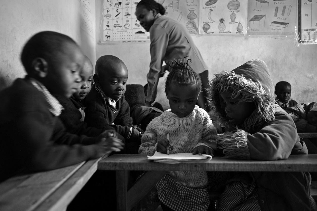 Ann Rose Nyambura, 3, is the center of attention as classmates observe her doing classwork. Their teacher is walking around the room collecting notebooks for grading.