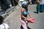A 12-year old Argentine girl, with her face covered in black makeup and dressed as a would-be prostitute, walks a street carrying an open purse asking for money.