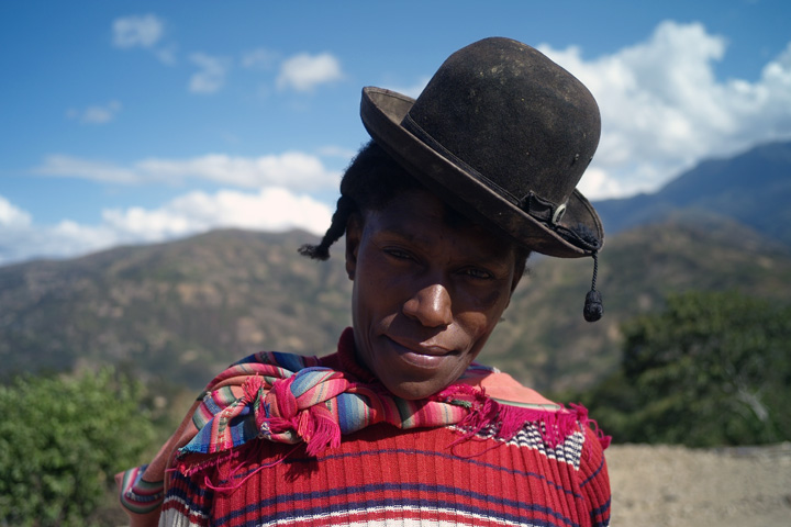 An Afro-Bolivian woman wearing a bowler hat, and standing outside in a tropical environment, looks into the camera.