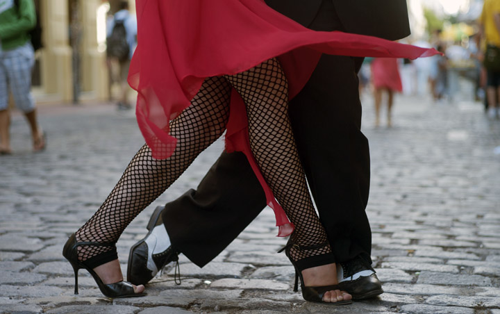 The lower bodies of an Argentinian couple are visible as they perform the Tango outside on a cobbled street - the woman's bright red dress sways to her movements.