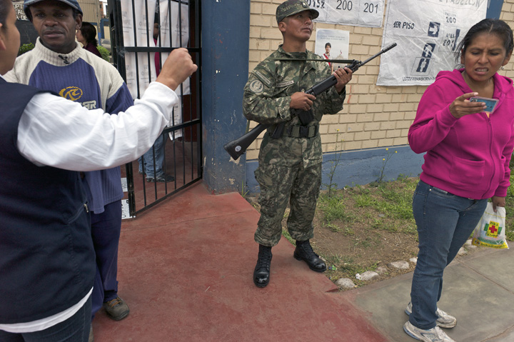 Standing outside an Afro-Peruvian man is directed by a female poll worker on where to cast his vote as a young Peruvian woman stands nearby along with a soldier holding a machine gun.