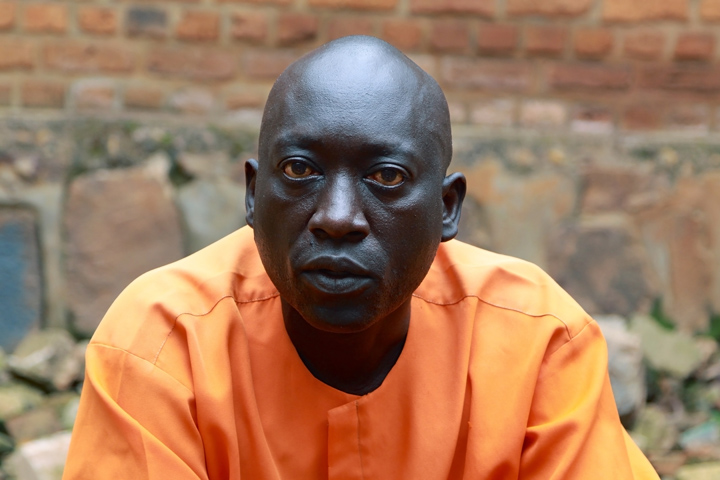 A male Rwandan inmate sits while looking directly into the camera during an interview; he's outdoors with a brick wall serving as a backdrop.