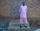 A 57-year old man, dressed in a pink prison uniform, stands outside on steps (facing the camera) with a brick wall behind him.