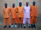 Five Rwandan men wearing prison uniforms are standing side-by-side (looking into the camera), outside with a brick wall as a backdrop.