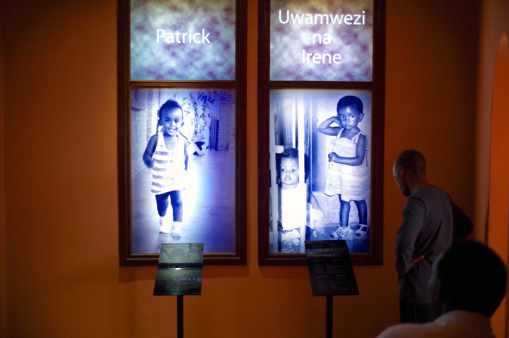 Inside a darkened memorial museum two black men (one seated the other standing) view the photographs and bios of three murdered Rwandan children.