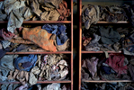 Tattered clothes are displayed inside two open wood cabinets in a dark room.