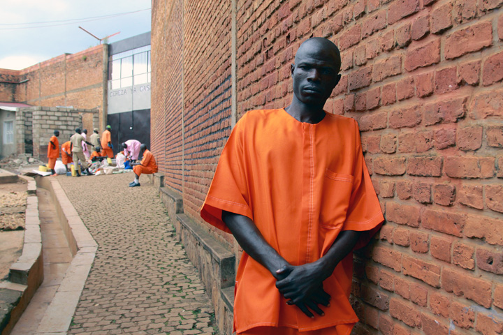 A 56-year old Rwandan man in an orange prison uniform leans against an outside prison wall; in the distant background are other inmates and guards.