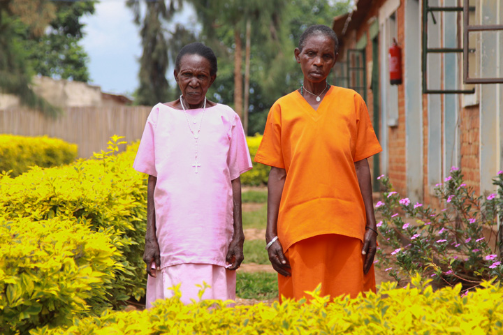 This is a portrait that features two Rwandan women (65 and 85 years old), wearing different colored prison uniforms, standing outside (side-by-side) and looking into the camera.
