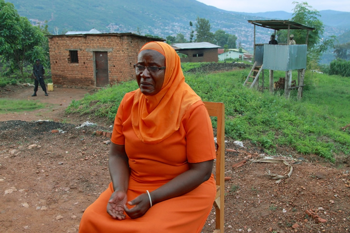 A 56-year old Rwandan woman, wearing a hijab and prison clothing, crys while sitting outside during an interview near an armed guard tower.