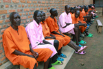 The shot shows a long line of men seated closely together; they're all wearing either an orange or pink prison uniform.