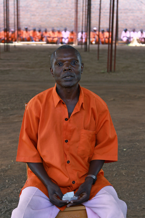 A 58-year old man, wearing a prison uniform, is seated on a chair holding a small piece of paper between his hands. In the distant background are other inmates in prison uniforms.