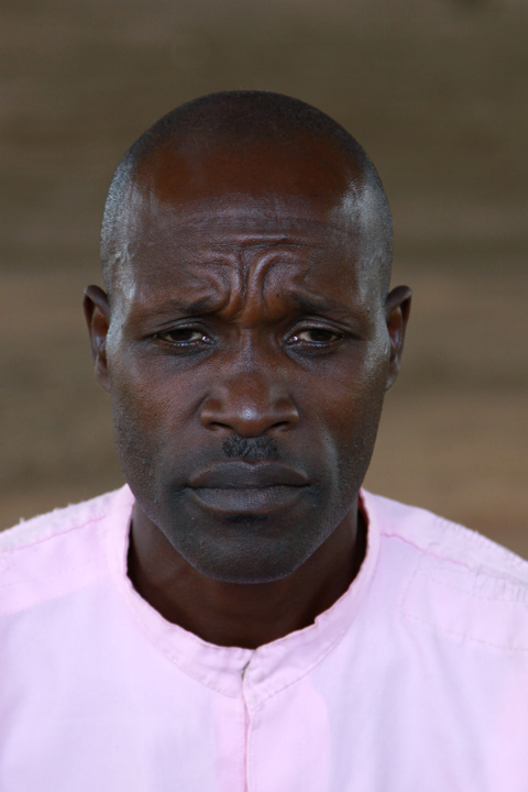 It is a head and shoulder photograph of a 40-year old man wearing a remorseful expression during an interview; he's dressed in a pink prison uniform.