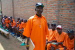 A 67-year old man, dressed in an orange prison outfit, stands facing the camera with a long line of similarly dressed inmates seated behind him.