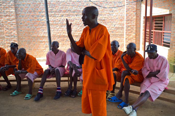 A 58-year old Rwandan male prisoner, dressed in a prison uniform, speaks at a group meeting; there are several inmates seated and listening in the background.