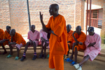 May 5, 2016 - Bugesera Prison - Emmanuel Cyimana, 58, was convicted of genocide in 1994. Here he's complaining to a prison official about the time he's serving; his sentencing records state that he must serve 24-years but prison officials say he's in for life. He discussed some of his crimes: {quote}I was urged to kill Tutsis and I did. I used traditional weapons. I shouted at those who tried to hide so that they could be discovered and killed. I did not have pity for anybody. I am sentenced to 24-years of imprisonment. I have been imprisoned since 1995. In the course of hunting Tutsis he described how a Hutu captured a man and cut him. {quote}I then cut him on his leg. My fellow killer said, 'do it seriously. Let me show you.' He cut off his head. On the third day of killing we found Antoinette Nyiramatama hiding. Dani Munyarugero cut her up immediately and Kamanazi removed the baby from her back and killed it. I was there with them. This is what I did.{quote}