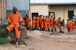 A 45-year old inmate sits outside facing the camera, as 16 fellow inmates are lined up, in the background, and searched as they wait to enter the prison yard - all are wearing orange prison uniforms.
