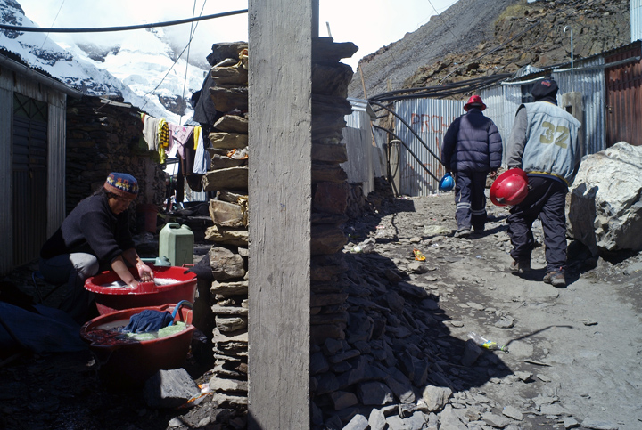 An indigenous woman washes clothes as miners return to the mountains.